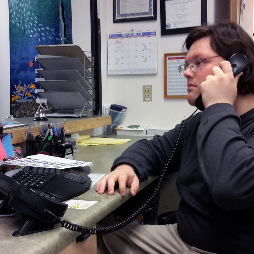 A REACH employee working at a desk and answering the phone